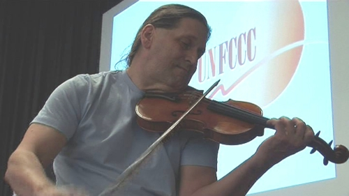 Aubrey Meyer playing the violin in front of a UNFCCC slide